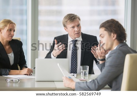 Furious boss scolding young frustrated intern with bad work results. Ineffective office worker receiving a dismiss notification sitting at the table, listen to irritated boss yelling  #582569749