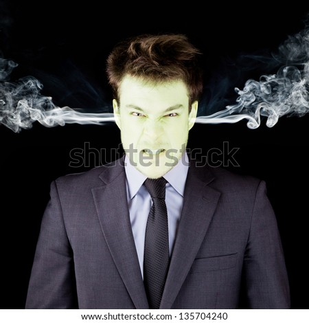 Furious businessman getting green isolated on black