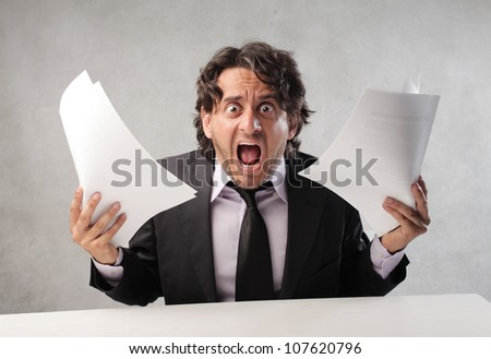 Furious businessman holding some documents