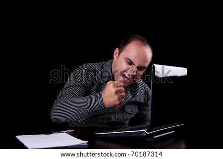 furious businessman looking to computer and taking notes, isolated on black background. Studio shot.
