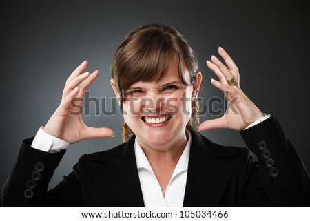 Furious businesswoman on gray background, studio shot