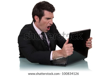 Furious man screaming in front of his laptop