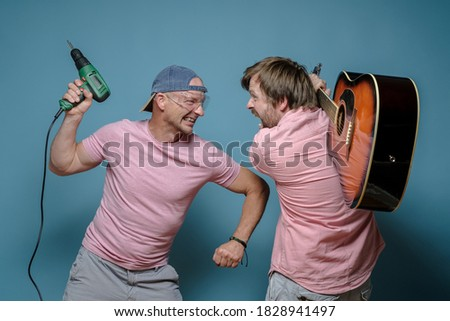 Furious musician and construction worker, they started a fight over the noise, one threatens with a drill, the other with a guitar. ストックフォト ©