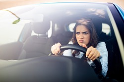 Furious woman stucked in traffic jam. A furiously angry woman driving grimaces, shaking her fist through the windscreen in a bout of road rage! Road rage traffic jam concep