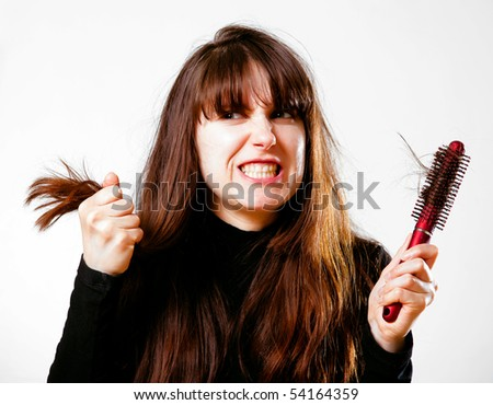 Furious woman with tangled hair holds a hairbrush in the hand