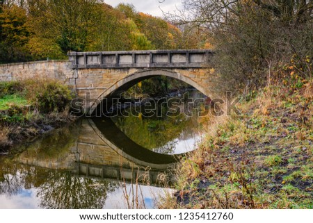 Furnace Bridge reflected in River Blyth, located in the Bedlington Country Park, Northumberland