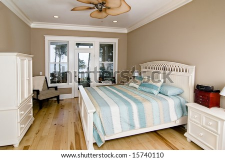 furnished bedroom with waterfront view out windows and glass door