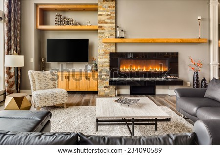 Furnished living Room in Luxury Home with Roaring Fire in Fireplace