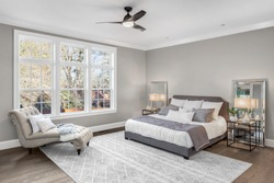 Furnished master bedroom in new luxury home with large windows and abundant natural light.  Features ceiling fan, nightstands with lamps, and additional furniture.