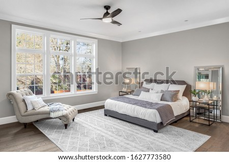 Furnished master bedroom in new luxury home with large windows and abundant natural light.  Features ceiling fan, nightstands with lamps, and additional furniture. Zdjęcia stock ©