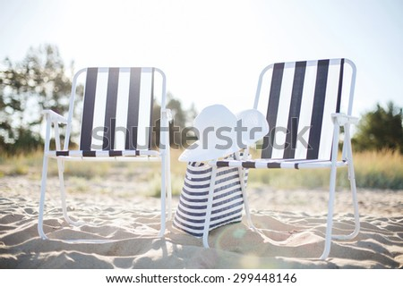 furniture and summer holidays concept - two beach lounges with beach bag and white hat on the beach