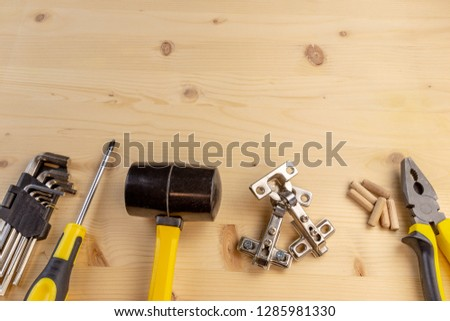 Furniture assembly components and tools arranged in a still life on a table. Background with copy space. #1285981330