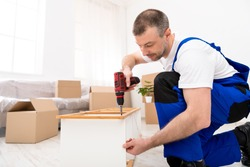 Furniture Assembly. Handyman In Coverall Uniform Assembling And Installing Shelf Using Electric Drill Screwdriver Working Indoors. Carpentry And Carpenter's Service, Repairman Working Fixing Furniture