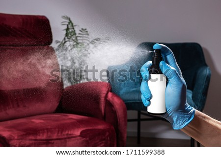 Photo of Furniture cleaning and refreshing. Spray for Care and Cleaning furniture. A hand in a medical glove sprays the detergent above sofa. Streak of droplets above the sofa, armchair.
