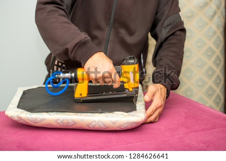 Furniture making. A man with a construction stapler makes furniture a wooden chair with a soft upholstery fabric. Furniture industry. Close up of a stapler in hand with upholstery for furniture.