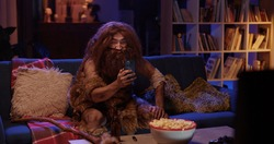 Furry bearded human ancestor in animal fur sitting on couch watching TV using mobile phone entertaining having fun party night at contemporary house.