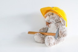 Furry, cuddly, cute little rabbit bunny toy in yellow helmet with hammer on white background with copy space