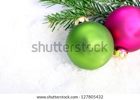 Fuschia and green Christmas baubles and pine tree branches on snow