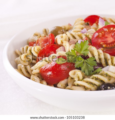 Fusili pasta salad, with rocket pesto, juicy tomatoes, olives and onion.