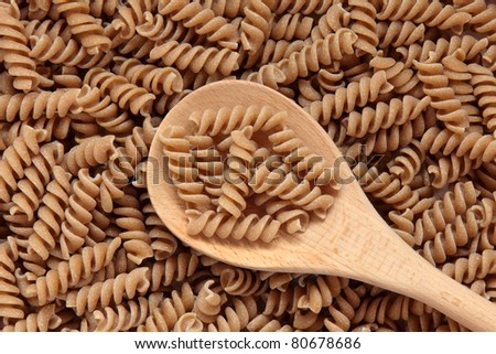 Fusilli pasta made with durham wheat in a wooden spoon and forming a background.
