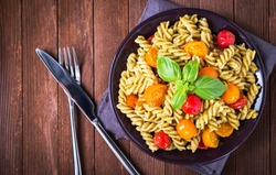 Fusilli pasta salad with pesto genovese, colorful tomatoes and basil leaves on dark wooden background top view. Italian food. Delicious meal. Traditional dish.