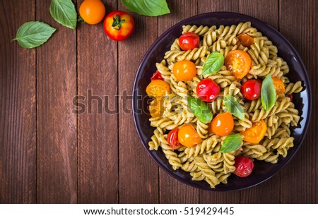 Fusilli pasta salad with pesto genovese, colorful tomatoes and basil leaves on dark wooden background top view. Italian food. Delicious meal. Space for text.