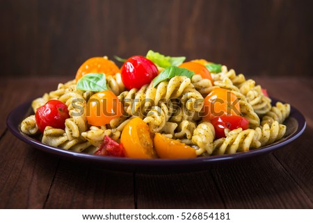 Fusilli pasta salad with pesto genovese, colorful tomatoes and basil leaves on dark wooden background close up. Italian food. Delicious meal.