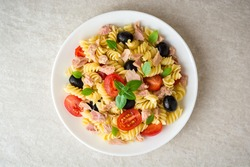 Fusilli pasta salad with tuna, tomatoes, black olives and basil on gray stone background. Top view.