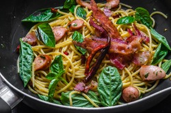 fusion food, spaghetti with fried crispy bacon ,sausage and basil leave, hot and spicy food, international cuisine