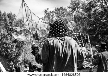 Fusion of cultural & modern music event. A black and white shot of a young male, viewed from behind, casting spiritual bubbles over tents during a festival celebrating native cultures.
