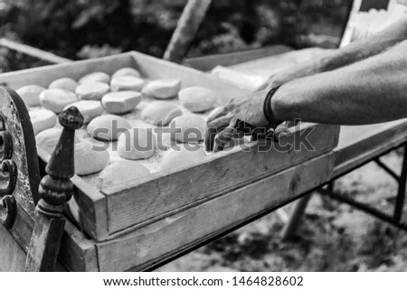 Fusion of cultural & modern music event. A black and white view of a baker preparing bread rolls using traditional methods, outdoors during a festival celebrating cultures and traditions close up shot #1464828602