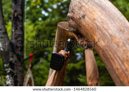 Fusion of cultural & modern music event. A close up view on the hands of a man using a cordless drill to join a rustic timber structure, construction of a teepee tent as hippies celebrate cultures.