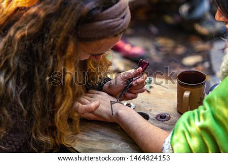 Fusion of cultural & modern music event. A person draws a symbolic henna tattoo on the hand and wrist of another at a campsite during a festival combining spiritual cultures #1464824153