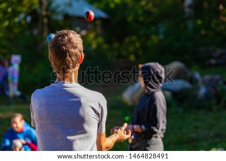 Fusion of cultural & modern music event. A rear view of a young Caucasian man, juggling balls as young people gather outside tents in the background, during a celebration of traditional cultures.