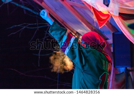 Fusion of cultural & modern music event. A side view of a male singer performing on stage by night, he raises his fist in the air as he faces the audience at a festival combining old and new cultures