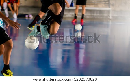 Futsal player  jump with trap and control the ball for shoot to goal. Soccer players fighting each other by kicking the ball. Indoor soccer sports hall. Football futsal player, ball, futsal floor.