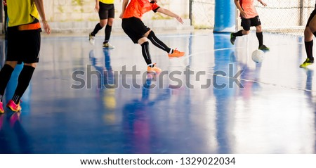 Futsal player  trap and control the ball for shoot to goal. Soccer players fighting each other by kicking the ball. Indoor soccer sports hall. Football futsal player, ball, futsal floor.