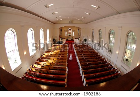 Future Bride - A young girl in a white dress walks down the center aisle of the church alone.