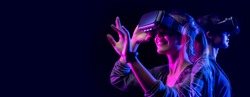 Future digital technology game and entertainment, Teenager having fun play VR virtual reality goggle, sport game 3D cyber space futuristic neon colorful background,