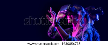 Future digital technology metaverse game and entertainment, Teenager having fun play VR virtual reality goggle, sport game 3D cyber space futuristic neon colorful background,