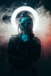Future girl. Cyberpunk portrait. Artificial life. Blue neon light Asian girl in black leather jacket glasses with glowing LED circle halo in red color smoke on dark night.