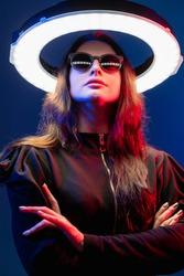Future girl. Cyberpunk portrait. Science fiction. Galaxy portal. Red neon light futuristic female alien in sunglasses with white LED circle halo illumination isolated on dark blue.