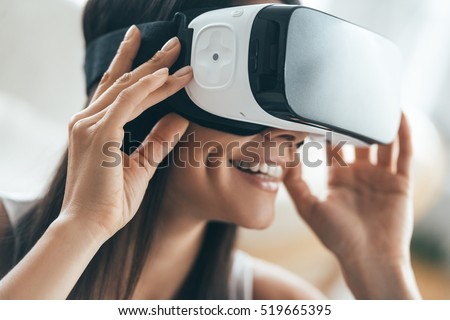 Future is now. Attractive young woman adjusting her VR headset and smiling while sitting at home