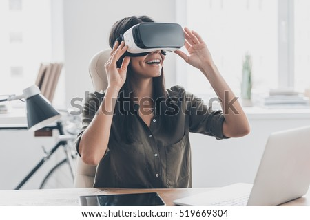 Future is right now. Confident young woman adjusting her virtual reality headset and smiling while sitting at her working place in office