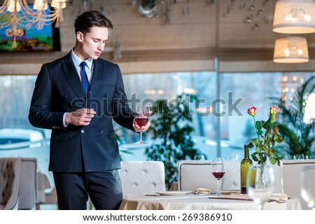 Future meeting. Young man businessman in formal wear standing in a restaurant while holding a glass of wine and looking forward