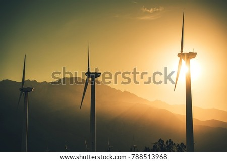 Future of Renewable Energy. Wind Turbines High Voltage Plantation at Sunset.