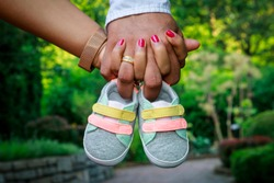 Future parents holding hands and a pair of little shoes over blur garden background. Concept of Parents-To-Be.