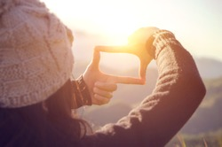 Future planning, Close up of woman hands making frame gesture with sunrise on mountain, Female capturing the sunrise, sunlight outdoor.