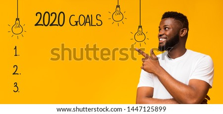 Future plans. Cheerful black man pointing at checklist with 2020 goals, yellow background