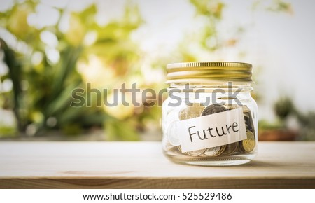 Future word with money coin in glass jar.For savings and financial investment concept ideas.